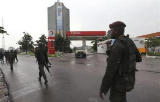 Congolese security forces secure the street near the state television headquarters in Kinshasa