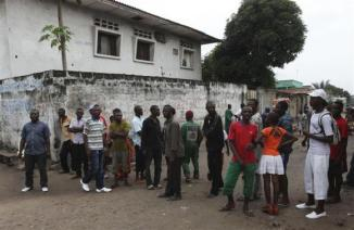 Residents gather to watch as security forces patrol the street near the state television headquarters in Kinshasa